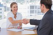 foto of interview  - Cheerful interviewer shaking hand of an interviewee during a job interview - JPG