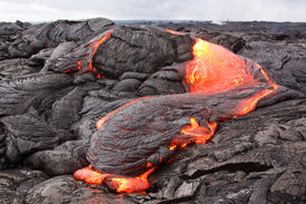 stock photo of magma  - Lava loses heat rapidly and its surface turns black and is pushed into wrinkles by moving interior - JPG