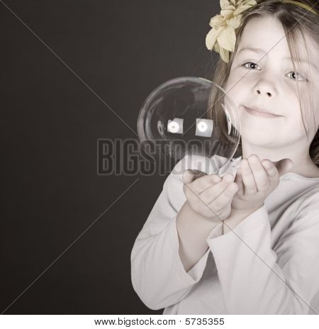 Shot Of A Cute Little Girl Catching A Bursting Bubble
