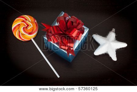 Blue Gift Box, Candycane And White Christmas Star On Black Wooden Background