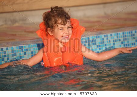 Little Girl In Inflatable Waistcoat In Pool