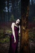 pic of pale skin  - Pale woman in purple dress lying upon a tree