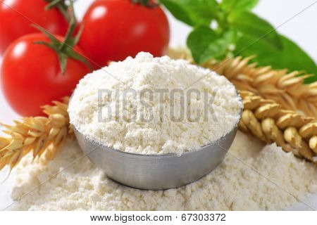 detail of small bowl with flour, wheat ear and fresh tomatoes