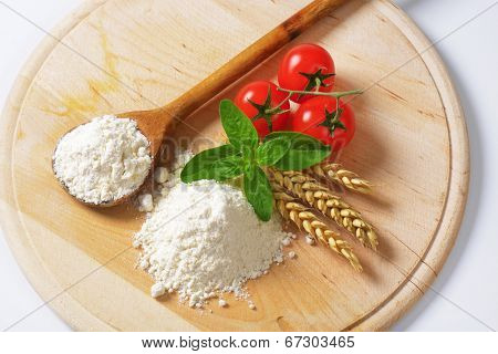 overhead view of soft wheat flour with wheat ear, wooden spoon and fresh tomatoes, on the wooden cutting board