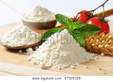 closeup of small piles of soft wheat flour with wooden spoon, wheat ear and fresh tomatoes