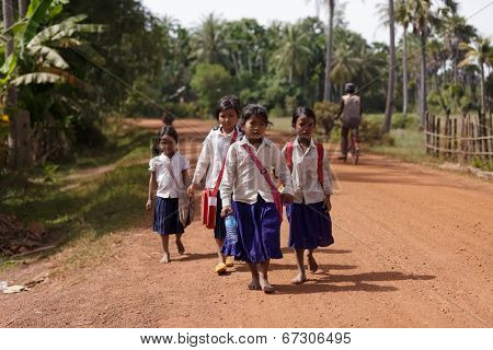 SIEM REAP, CAMBODIA, DECEMBER 04 : Cambodian little girls students in traditional clothes walking on a countryside dirt road near Siem Reap, Cambodia on December 04, 2012