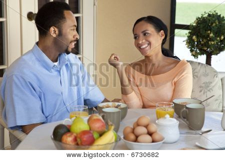 Happy African American Couple Sitting Outside Having A Healthy Breakfast