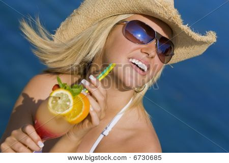 Beautiful Blond Woman Drinking Cocktail By The Sea