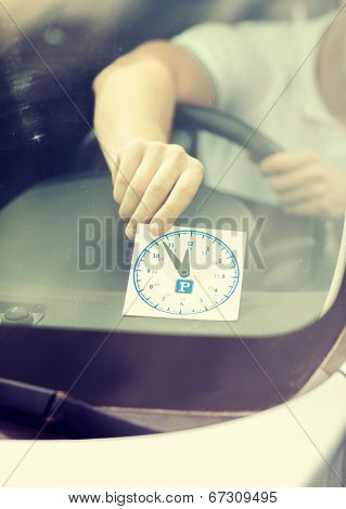 transportation and vehicle concept - man placing parking clock on car dashboard under windscreen