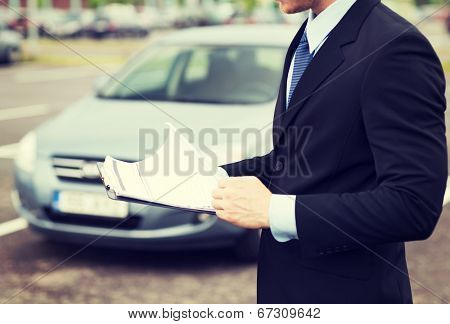 transportation and ownership concept - man with car documents outside