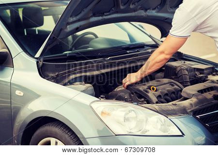 transportation and vehicle concept - man opening car bonnet and looking under hood