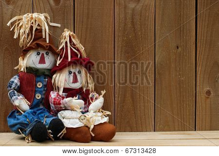 Scarecrows sitting by rustic wooden fence