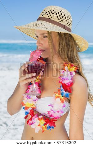 Pretty blonde in floral garland sipping cocktail on the beach on a sunny day