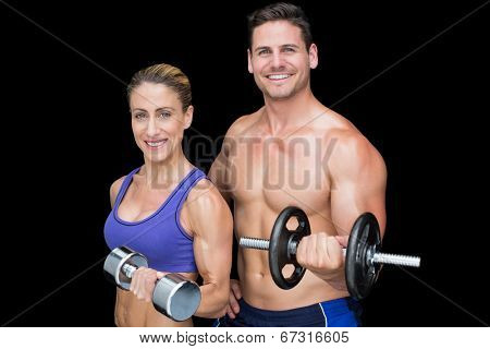 Crossfit couple posing with dumbbells smiling at camera on black background