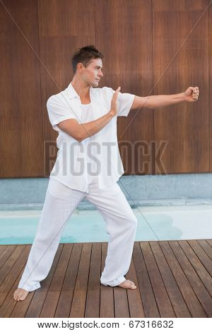 Handsome man in white doing tai chi in health spa