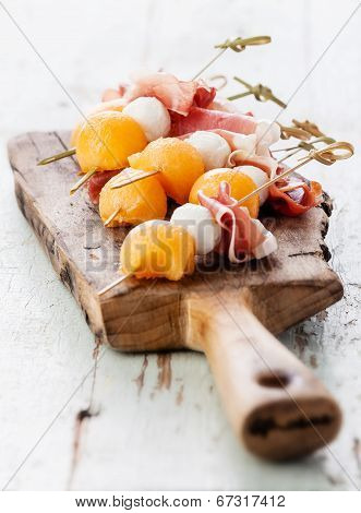 Mozzarella, Prosciutto, Melon Canapes On Textured Background