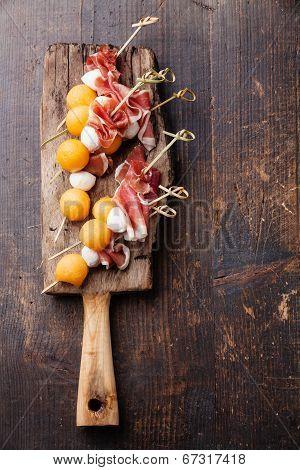 Mozzarella, Prosciutto, Melon Canapes On Wooden Background