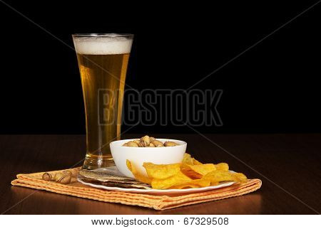Dish with chips, pistachios and salty fish, beer