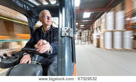 Elderly man driving a forklift through a warehouse where cardboard boxes are stored.