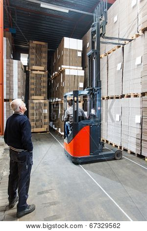 Supervizor oversees a pallettruck reaching high up while grabbing a pallet from the top shelf