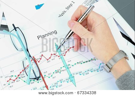 Young Businesswoman Working In The Office,  Sitting At Her Desk, Analyzing  Data In  Graphics.