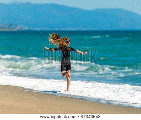 little girl in a wetsuit running along the coast. back view