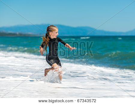 laughing little girl jumping in a wetsuit on the beach