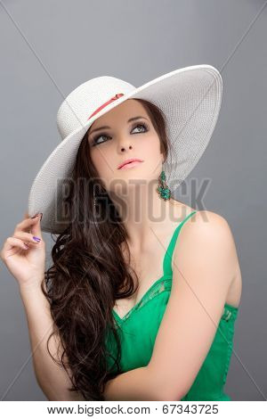 Portrait of a beautiful young brunette woman. Wearing white hat over long loose curly hair. Open shoulders summer emerald green dress. Against grey studio background.
