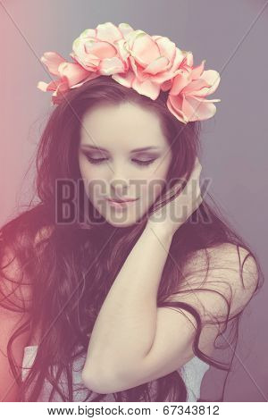 portrait romantic of beautiful woman with long curly brown hair wearing pink flower crown