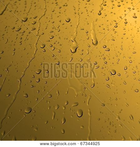 Water drops on yellow glass