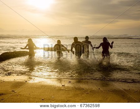 Silhouettes Of Friends Running Out Of The Ocean