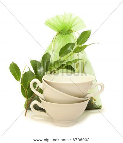 Porcelain Cups, Green Leaves And A Bag Of Tea