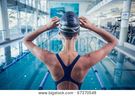 Pretty swimmer standing by the pool at the leisure center