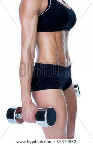 Female bodybuilder working out with large dumbbells mid section on white background
