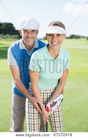 Golfing couple putting ball together smiling at camera on a sunny day at the golf course