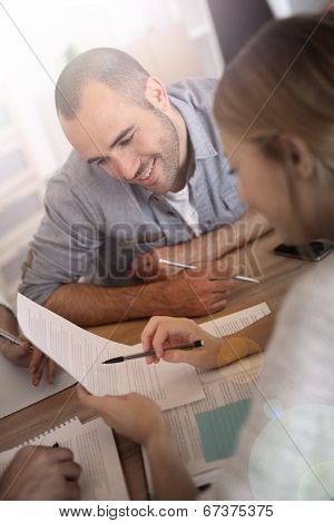 Man reading contract commented by business partner