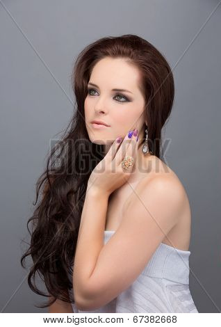 Portrait of beautiful young brunette woman. Wearing long loose curly hair. Against grey studio background.