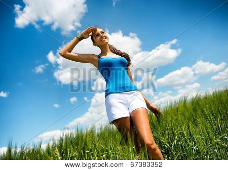 Young woman enjoying the warm summer sun standing in a green field with her head raised with a smile of pleasure