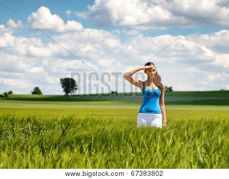 Beautiful young woman turning to smile at the camera with her hand raised to shield her eyes from the sun as she stands in a scenic green field in the countryside