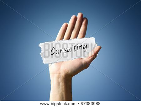 Man holding up a scrap of white paper with the word - Consulting - in script, close up of his hand on a blue background with a side vignette in a conceptual image