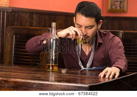 man in suit drinking alcohol shot