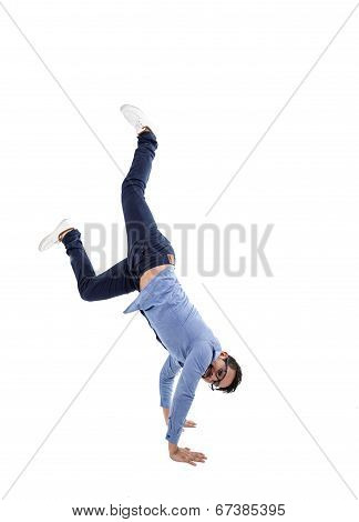 young hispanic man with blue shirt and glasses doing cartwheel