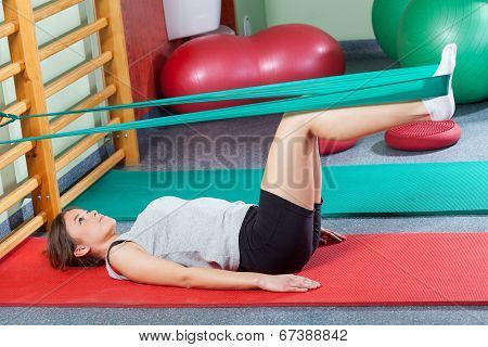 Girl Lying On Exercise Mat And Stretching Legs