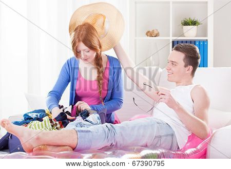 Young Couple Unpacking Luggage And Relaxing