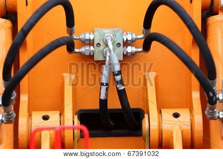 Multiple Black Hydraulic Hoses On An Excavator