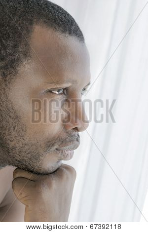 Young Afro man concerned, side view