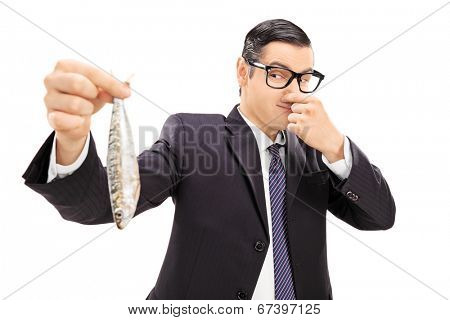 Young businessman holding a stinky fish isolated on white background