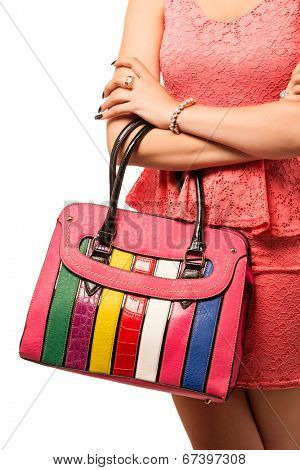 Woman wearing pink lace mini dress. With bright stripe candy fashion bag. Isolated on white studio background