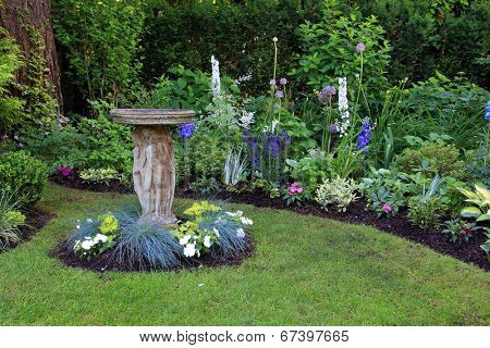 Bird bath in a beautiful summer garden.