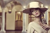 stock photo of aristocrat  - fashion girl with big elegant hat and foulard on the head posing with beige dress and sensual expression - JPG